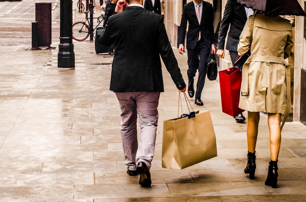 Bond Street - A man and woman carrying shopping bags in luxury retail area of London